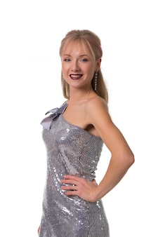 Muchacha rubia hermosa que presenta en un blanco en los vestidos brillantes, aislados