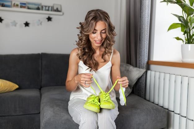 La muchacha rubia hermosa en verde de la camisa de vestir blanca se divierte las zapatillas de deporte que se sientan en el sofá