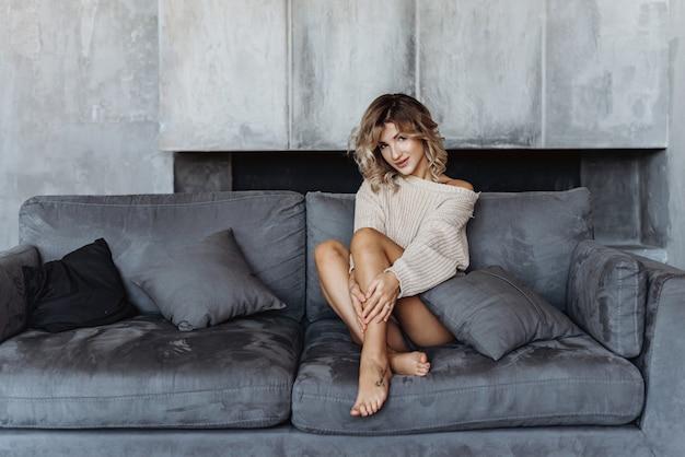 La muchacha rubia joven en un suéter se sienta en el sofá