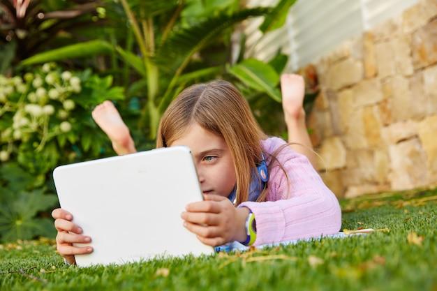 Muchacha rubia del niño con la pc de la tableta que miente en césped de la hierba