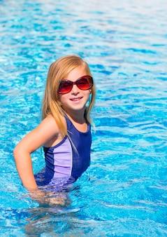 Muchacha rubia del niño en la piscina azul posando con gafas de sol