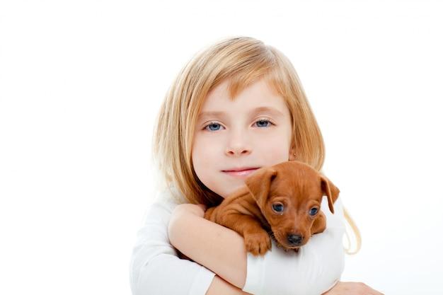 Muchacha rubia de los niños con el perrito mini pinscher del perro