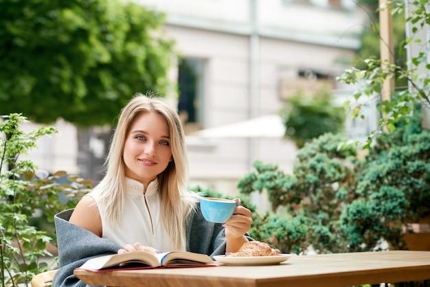 Muchacha rubia que bebe el café en el salón del café al aire libre que mira la cámara.
