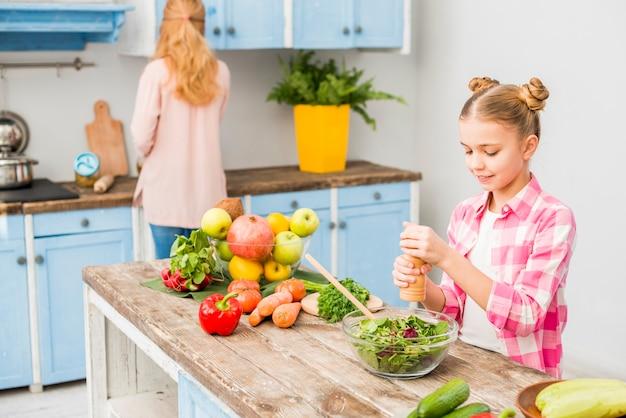 Muchacha rubia que muele la pimienta en cuenco de ensalada con su madre en la cocina