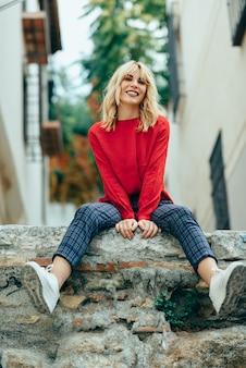 Muchacha rubia sonriente con la camisa roja que disfruta de vida al aire libre.