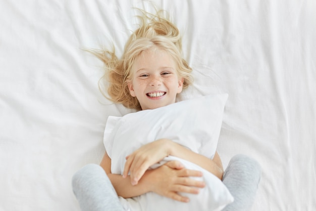 Muchacha rubia sonriente que abraza la almohada blanca mientras que está en la guardería, tiene buen humor mientras ve a alguien y se acuesta en la cama blanca. pequeña niña adorable que tiene hora de acostarse. concepto de descanso