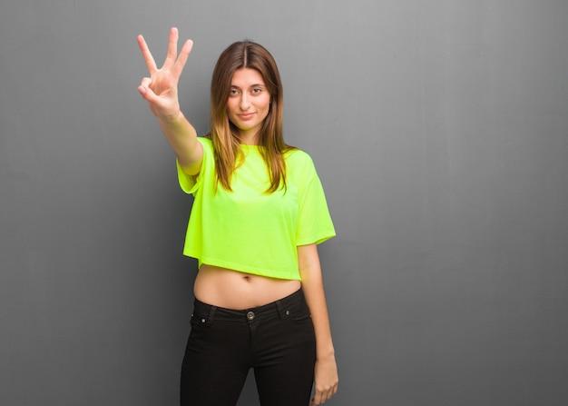 Muchacha rusa fresca joven que muestra el número tres
