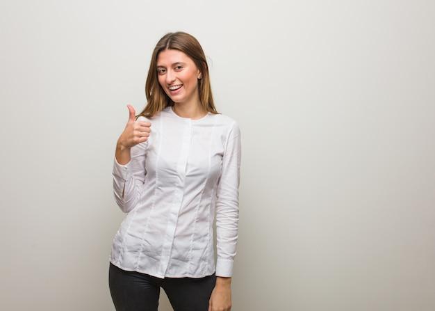 Muchacha rusa joven que sonríe y que levanta el pulgar para arriba