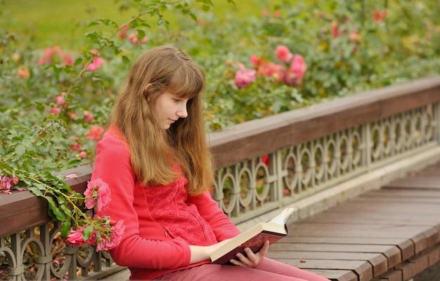 La muchacha está sentada en el banco y leyendo el libro, otoño.