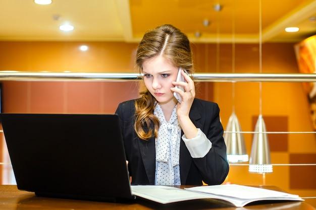 Muchacha seria joven que se sienta en un café con un ordenador portátil y que habla en el teléfono móvil