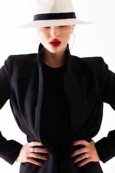 Muchacha en un sombrero blanco y una chaqueta negra en una pared aislada blanca. labios sexy rojos.