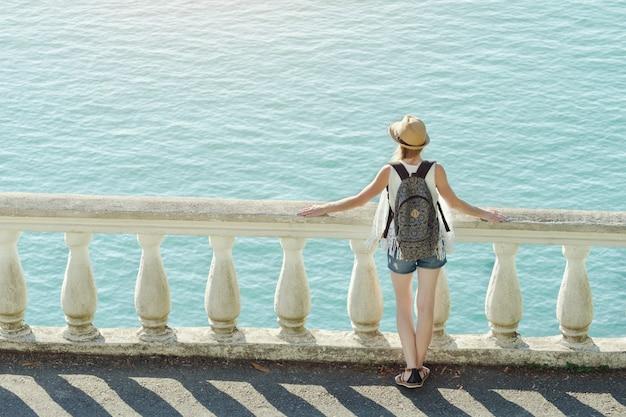 Muchacha en el sombrero que se coloca en el balcón y que mira el mar. vista trasera