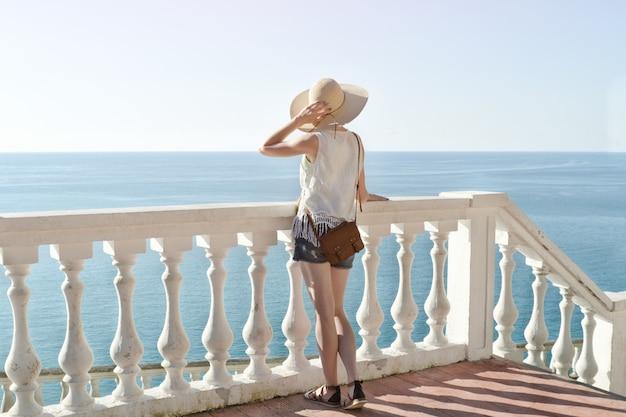 Muchacha en el sombrero que se coloca en las escaleras y que mira el mar. vista trasera