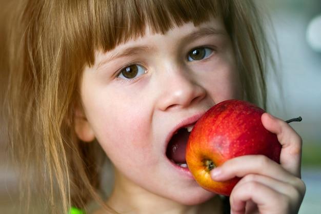 La muchacha sonríe y sostiene una manzana roja.