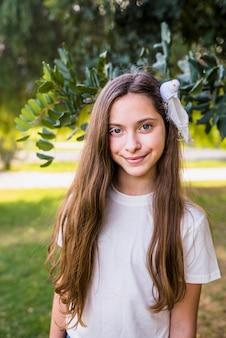 Muchacha sonriente adorable que se coloca delante de un árbol en parque
