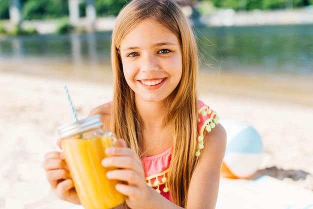 Muchacha sonriente alegre con la bebida en costa