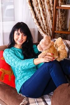 La muchacha sonriente alegre que se sentaba en el sofá en la navidad adornó el interior, sosteniendo los juguetes de los osos.