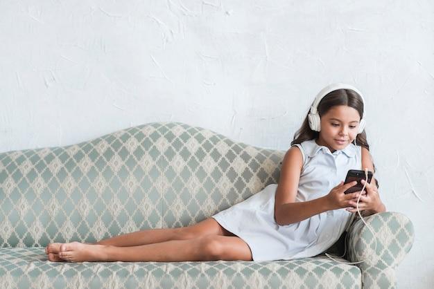 Muchacha sonriente con el auricular en su cabeza que mira el teléfono móvil