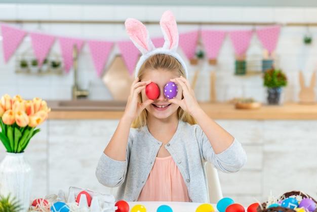 La muchacha sonriente cierra sus ojos con los huevos de pascua en la cocina.