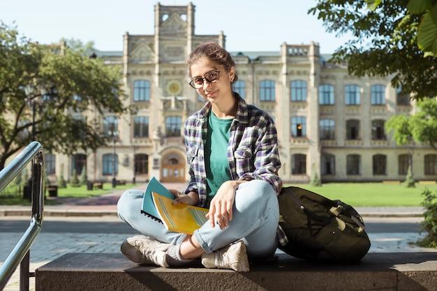 Muchacha sonriente del estudiante indio que se sienta cerca de universidad. mujer joven feliz en vasos con libros.