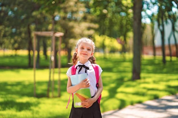 Muchacha sonriente del estudiante que lleva la mochila escolar y que sostiene el libro de ejercicio