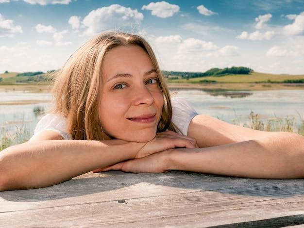 La muchacha sonriente joven está inclinando sus manos en la tabla de madera, y está mirando la cámara en fondo del paisaje del país del verano.