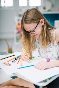 Muchacha sonriente con el lápiz que pinta en el papel en la tabla en sitio
