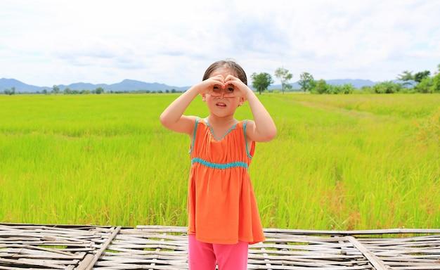Muchacha sonriente del niño que se coloca en los campos de arroz verdes jovenes con la fabricación del corazón de la muestra en ojos