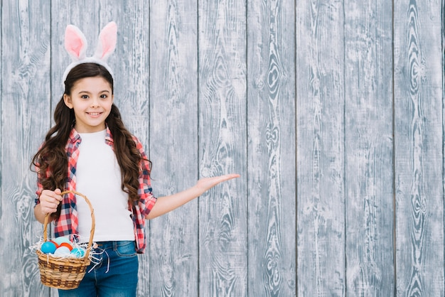 Muchacha sonriente con los oídos del conejito que sostienen la cesta de huevos de pascua que presentan contra el escritorio de madera gris