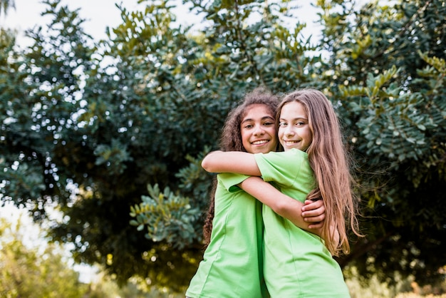 Muchacha sonriente que se abraza contra árbol verde