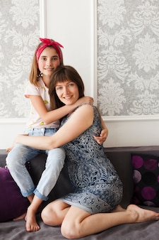 Muchacha sonriente que abraza a su madre y que mira la cámara mientras que se sienta en el sofá