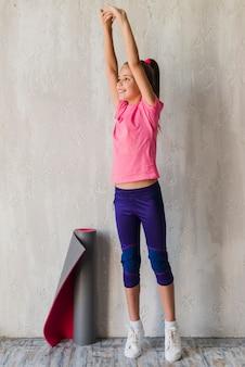 Muchacha sonriente que se coloca delante del muro de cemento que estira su mano