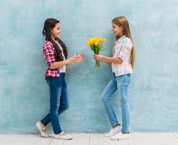 Muchacha sonriente que da la flor amarilla del tulipán a su amigo contra la pared azul