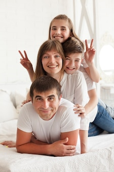 Muchacha sonriente que gesticula la muestra de la victoria en cama con su padre y hermano