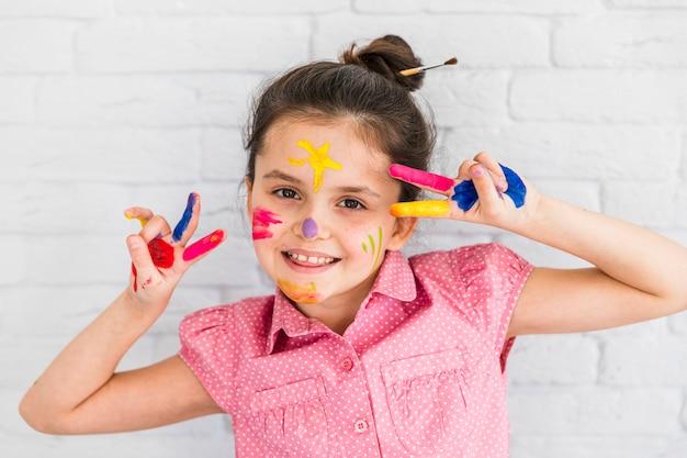 Muchacha sonriente que hace gesto de la paz con los dedos y la cara pintados contra la pared de ladrillo blanca