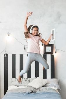 Muchacha sonriente que lleva el auricular que salta sobre la cama con la tableta digital