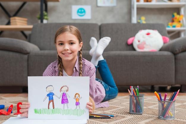 Muchacha sonriente que miente en la alfombra que muestra el dibujo de su familia dibujado en el libro blanco