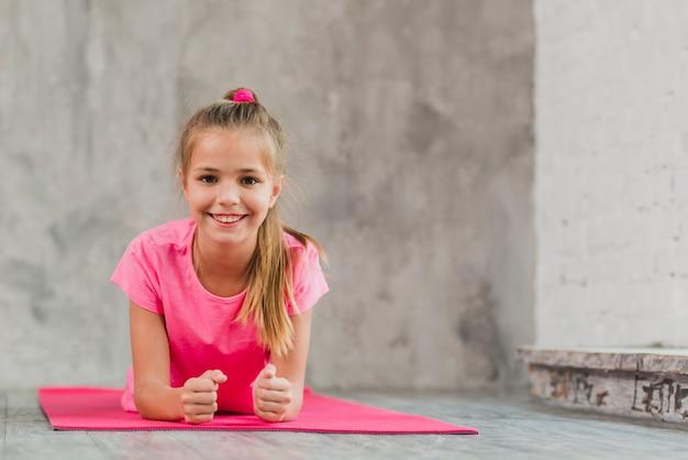 Muchacha sonriente que miente en la estera rosada del ejercicio contra el contexto concreto