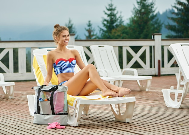Muchacha sonriente que miente en el ocioso blanco cerca de la piscina.
