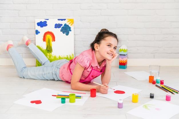 Muchacha sonriente que miente en la pintura del piso en el libro blanco con el cepillo rojo