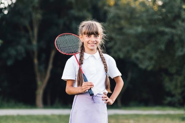 Muchacha sonriente que sostiene el bádminton que se coloca en el parque