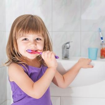 Muchacha sonriente que sostiene el cepillo de dientes que se coloca delante del fregadero del servicio