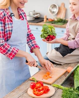 Muchacha sonriente que sostiene el rábano en la mano que ayuda a su madre que corta la zanahoria con el cuchillo en la tajadera