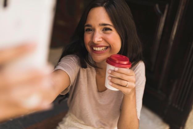 Muchacha sonriente que sostiene la taza de café para llevar que toma el selfie del smartphone