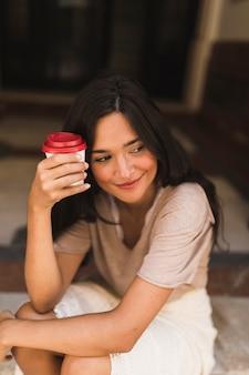 Muchacha sonriente que sostiene la taza de café para llevar