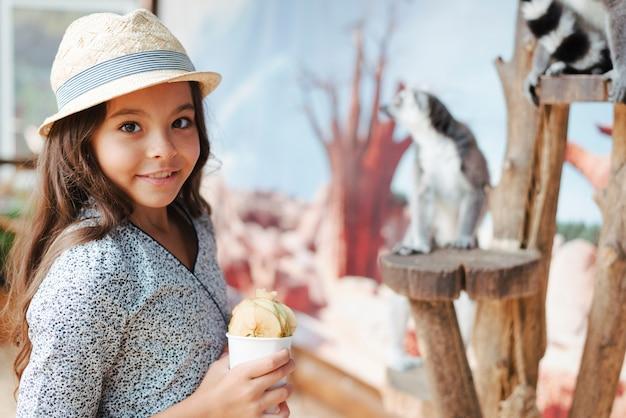 Muchacha sonriente que sostiene el vidrio de rebanadas de la manzana en el parque zoológico