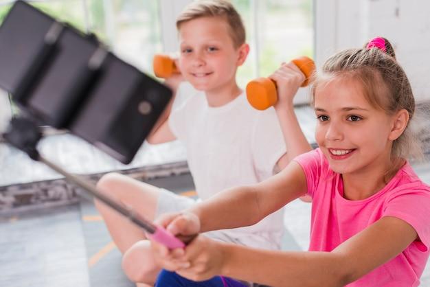 Muchacha sonriente que toma el selfie en el teléfono móvil que se sienta con su amigo que ejercita con pesas de gimnasia