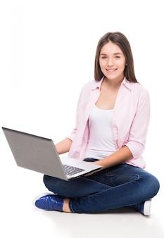 La muchacha sonriente con se está sentando en el suelo con la computadora portátil.