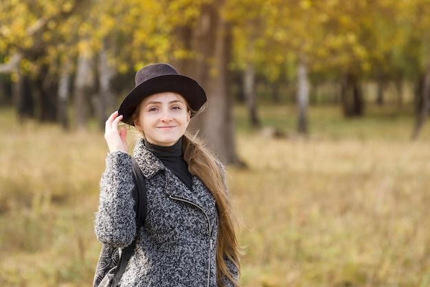 Muchacha sonriente en un sombrero que se coloca en el bosque del otoño.