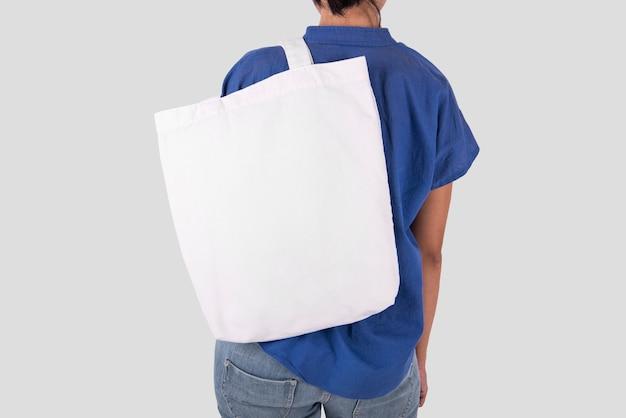 La muchacha está sosteniendo la tela de la lona del bolso para la plantilla en blanco de la maqueta aislada en fondo gris.
